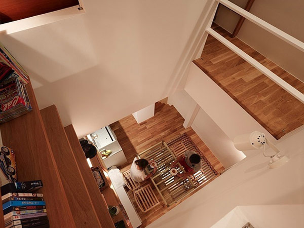 Narrowhouse-with-wooden-furniture-viewed-by-up-floor-with-white-wall-laminate-flooring-wooden-chase-some-books-and-unique-table-at-basic-floor-and-chair