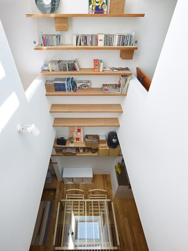 Viewed-by-up-point-of-view-with-wooden-chase-at-white-wall-books-pot-flower-and-the-basic-floor-with-laminate-flooring-glass-table-wooden-chair