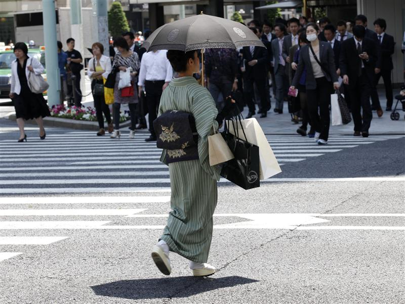 "A woman in a traditional ""Kimono"" carries shopping bags at a shopping district in Tokyo"