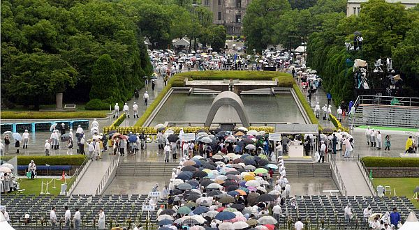 People wait in queue to offer prayers for the victims of the 1945 atomic bombing, in the rain at the Peace Memorial Park in Hiroshima