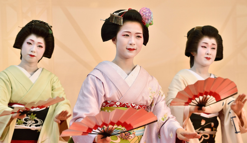 A maiko (C), an apprentice geiko, and geikos from Japan's ancient capital Kyoto, perform a traditional dance during a special event as part of the Kyoto summer travel campaign in Tokyo on June 21, 2015. The event was held to promote Kyoto tourism.    AFP PHOTO / KAZUHIRO NOGI