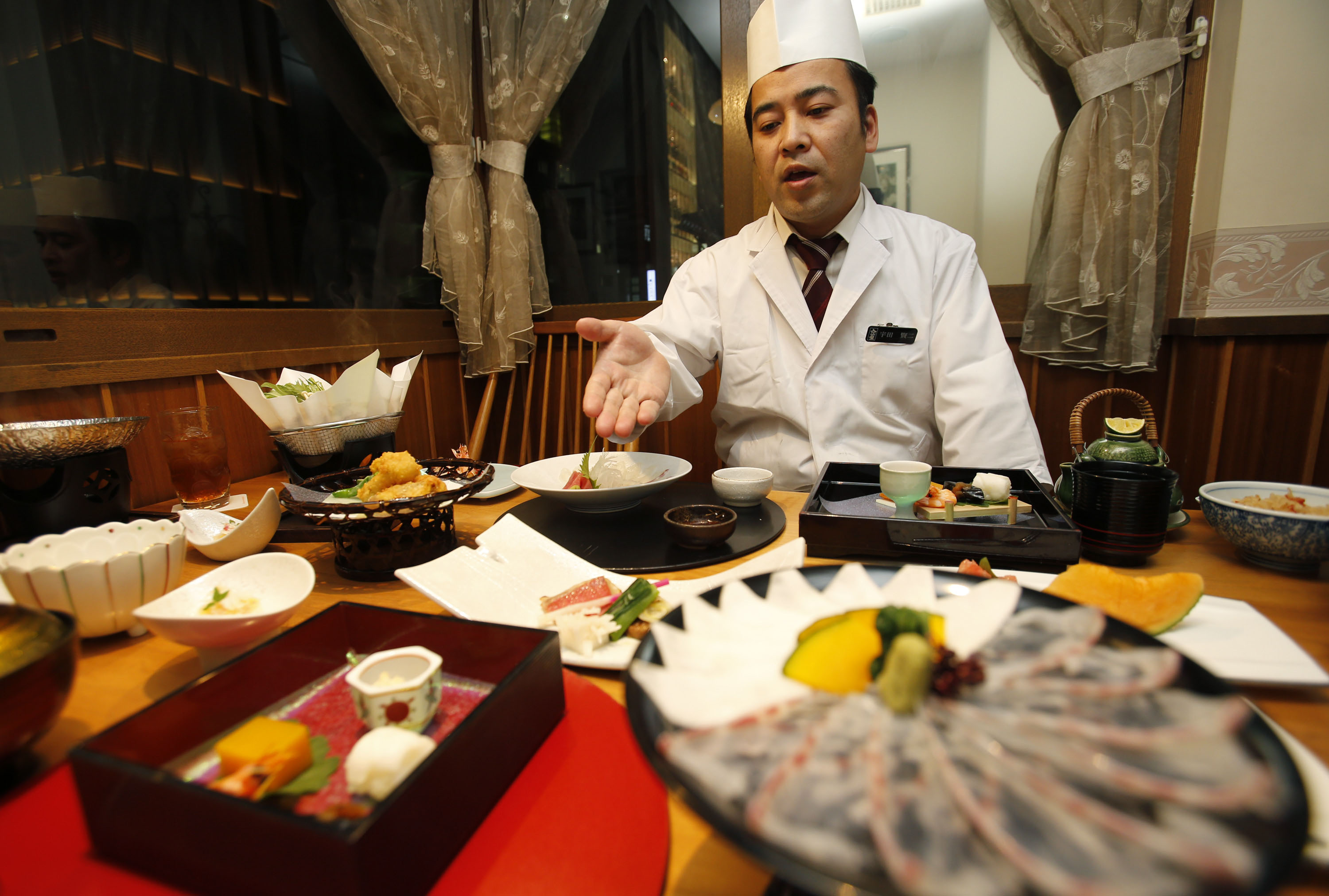 In this Wednesday, Nov. 27, 2013 photo, chief chef Kenji Uda explains about the menu at Japanese restaurant Irimoya Bettei in Tokyo. Washoku, the traditional cuisine of Japan, is being considered for designation as part of the worldfs priceless cultural heritage by the U.N. this week. But even as sushi and sake booms worldwide, purists say its finer points are candidates for the endangered list at home. The younger generation is increasingly eating Krispy Kreme donuts and McDonaldfs, not rice. Uda, 47, says he was 17 when he decided to devote his life to washoku. gJapanese food is so beautiful to look at,h he said. gBut it takes a lot of time. People are working and busy, and no longer have that kind of time.h (AP Photo/Shizuo Kambayashi)