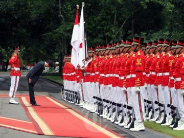 Japanese Prime Minister Shinzo Abe pays tribute to Indonesian and Japanese flags at the State Palace in Jakarta on Jan. 18, 2013