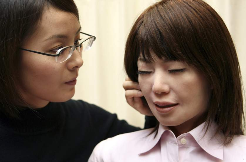 Andoroid Repliee Q2 reacts as graduate student Motoko Noma touches her face in Tokyo