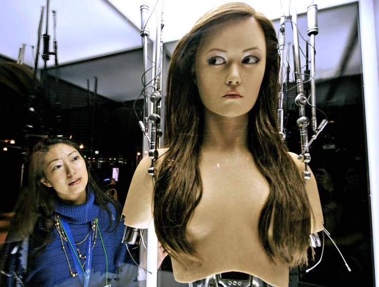 A woman watches a full-scale figure of a