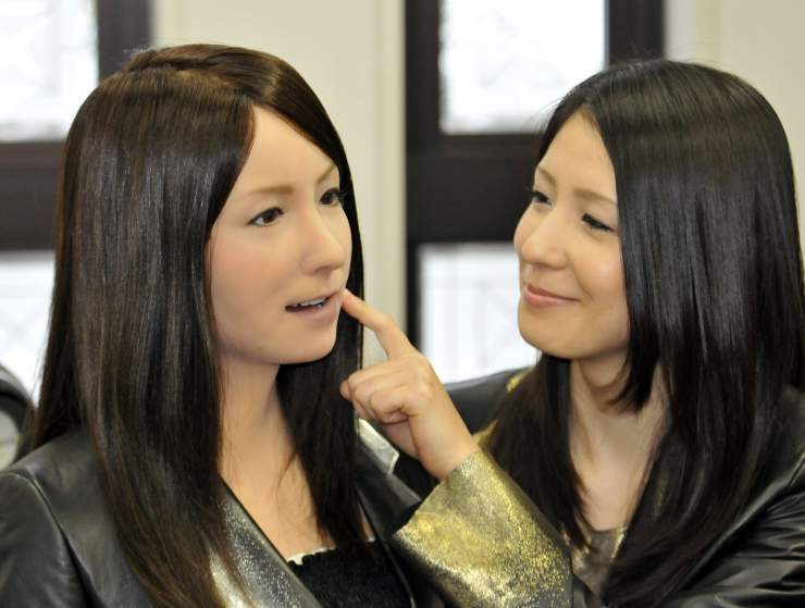 A model (R) pokes the face of a humanoid